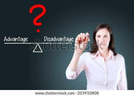 Young business woman writing advantage and disadvantage compare on balance bar. Blue background. - stock photo