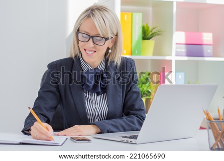 Young business woman writing to do list while sitting at her desk - stock photo