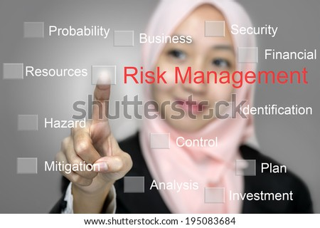Young Business Women press digital RISK MANAGEMENT button on interface in front of her