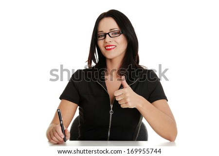 Young business writing and showing ok, sitting by a desk. Isolated on white. - stock photo