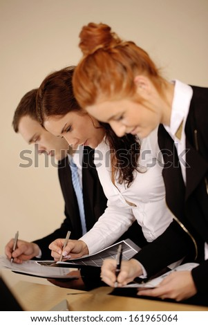 Young business writing on documents and analyzing them. - stock photo