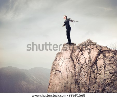 Young businessman about to fly from a mountain peak - stock photo