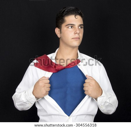 Young businessman acting like a super hero and tearing his shirt off with copy space - stock photo