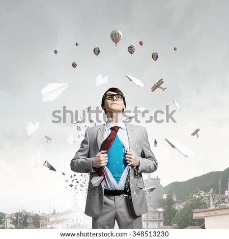 Young businessman acting like super hero and tearing his shirt off and looking up - stock photo