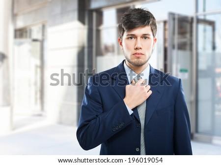 Young businessman adjusting his necktie - stock photo