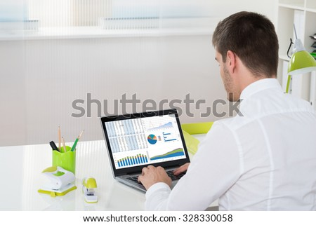 Young Businessman Analyzing Graph On Laptop In Office - stock photo