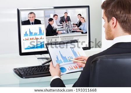 Young businessman analyzing graphs while video conferencing with colleagues on computer at office desk - stock photo