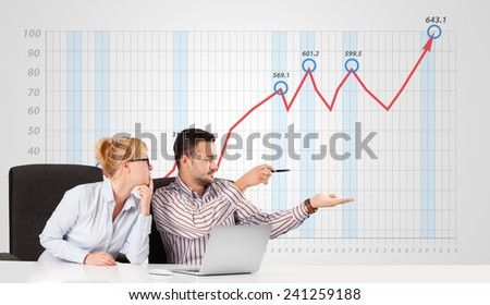 Young businessman and businesswoman calculating stock market with rising graph in the background - stock photo
