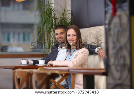 Young businessman and businesswoman drinking coffee at the coffee shop - stock photo