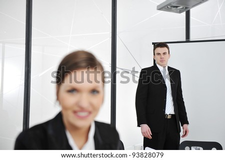 Young businessman and businesswoman in business presentation at office, looking at camera smiling - stock photo