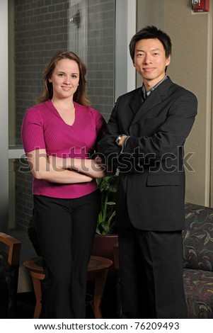 Young businessman and businesswoman inside an office building - stock photo