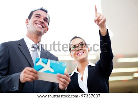young businessman and businesswoman looking at boarding information at airport