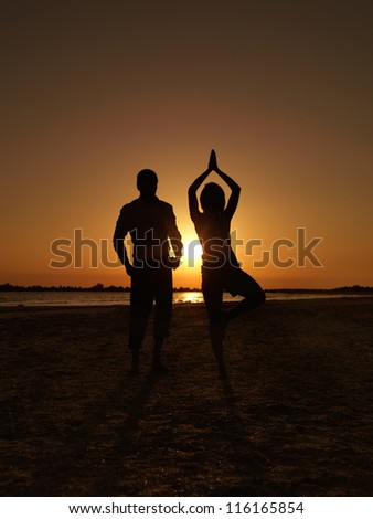 young businessman and businesswoman on the sea shore, standing in a yoga position, meditating at sunset - stock photo