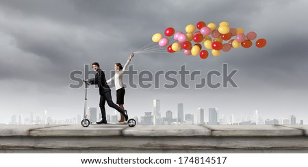 Young businessman and businesswoman riding scooter on roof of building