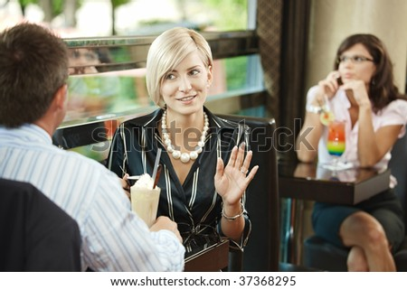 Young businessman and businesswoman sitting at table in cafe, talking.