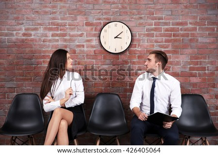 Young businessman and businesswoman sitting on a chairs in brick wall hall