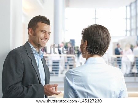 Young businessman and businesswoman talking outdoors, smiling happy. - stock photo