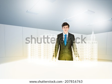 Young businessman and digital model of construction project