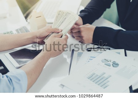 Young businessman and home buyer customer had achieve target means together and signed in the contract of sale of real estate and paying down payment to realtor