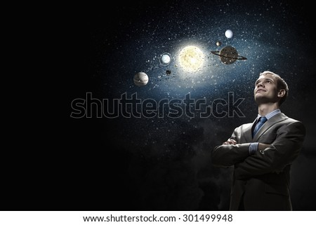 Young businessman and planets of sun system - stock photo