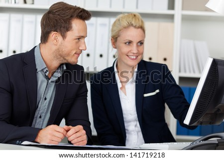 Young businessman and woman using computer in meeting at office desk - stock photo