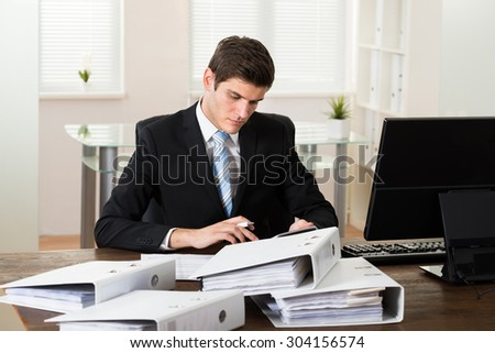 Young Businessman At Desk Doing Accounting In Office - stock photo