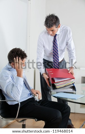 Young businessman at desk overwhelmed by load of work - stock photo