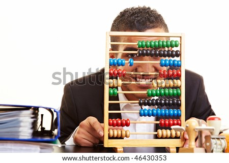 Young businessman at his desk with an abacus - stock photo