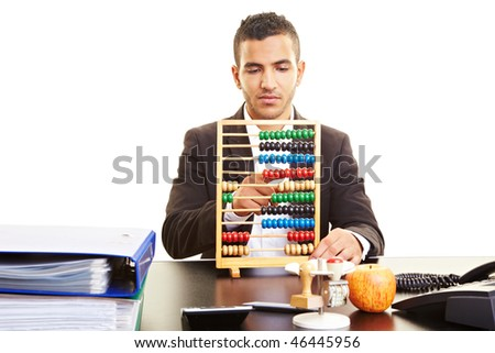 Young businessman at his desk with an abacus