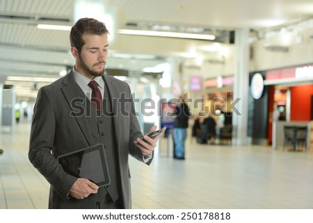 Young Businessman at the airport holding his phone and tablet - stock photo