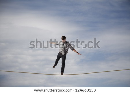 Young businessman balancing on a rope in the sky.