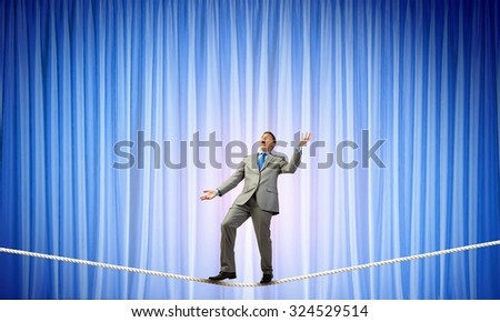 Young businessman balancing on rope and juggling with balls - stock photo
