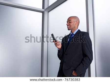 Young businessman beside an office window looking at his cell phone, smiling. - stock photo