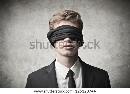 Young businessman blindfolded - stock photo