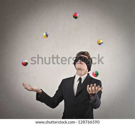 young businessman blindfolded playing with balls - stock photo