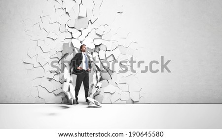 Young businessman breaking trough a wall - stock photo