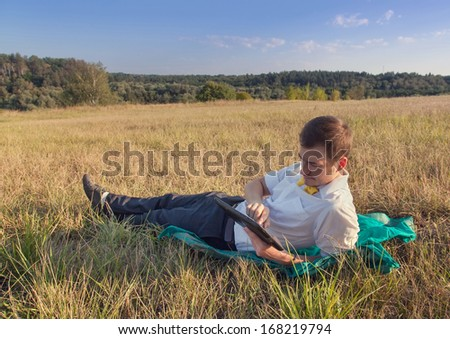 Young businessman browsing in Internet on pad outdoor  - stock photo