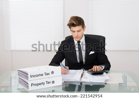 Young businessman calculating tax with binders at desk in office - stock photo