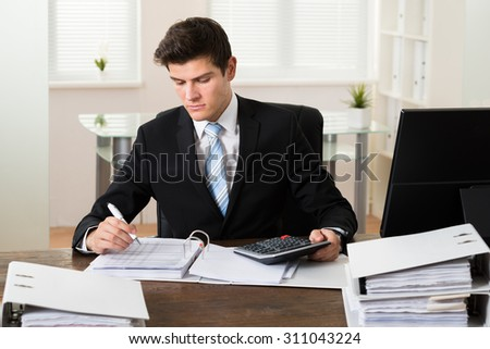 Young Businessman Calculating Tax With Calculator In Office