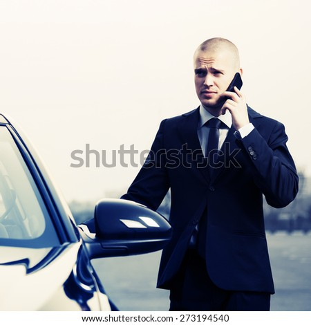 Young businessman calling on the phone next to car - stock photo