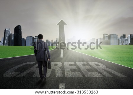 Young businessman carry a briefcase and walk on the path with a career text going up as an arrow