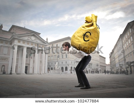 Young businessman carrying a money-bag on his shoulders on a town square - stock photo