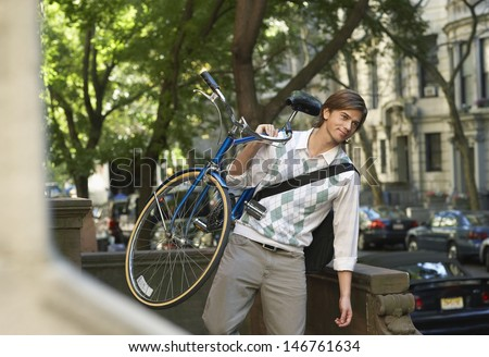Young businessman carrying bicycle outdoors - stock photo