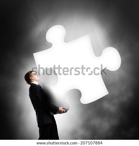 Young businessman carrying huge piece of puzzle - stock photo