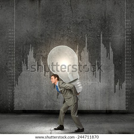 Young businessman carrying light bulb on back - stock photo