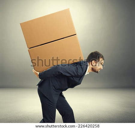 young businessman carrying two cardboard heavy boxes. photo in the dark room