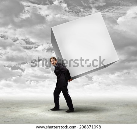 Young businessman carrying white big cube. Place for text - stock photo