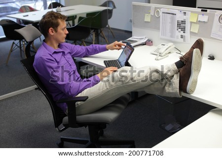 Young businessman caucasian in his office working with tablet - relaxed sitting position with legs on desk - stock photo
