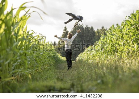 Young businessman celebrating his business freedom and success by throwing his suit jacket in the air standing in grassland between two cornfields. - stock photo