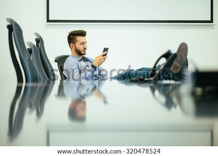 Young businessman CEO waiting for the meeting in the conference room. - stock photo
